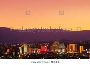 Reno, Nevada skyline at dusk with the Sierra Nevada Mountains in distance.