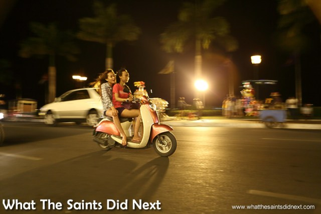 Young girls out for the night on the Riverside in Phnom Penh. Watching Cambodia Traffic.