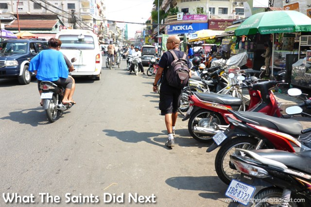 Here I am (a different day) having to walk on the street as the pavements are occupied by street vendors and mopeds. Walking The Streets Of Phnom Penh.