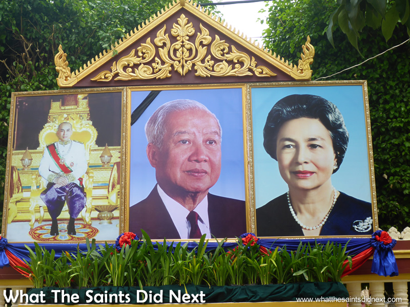 Portraits of King Norodom Sihamoni of Cambodia (left) and his parents outside the walls of the Royal Palace Phnom Penh Cambodia.