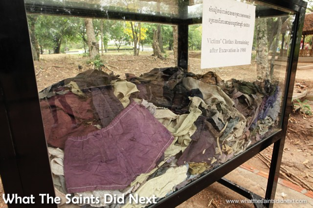 Rags of Victims' Clothes - After the mass graves were exhumed in 1980, these rags of victims' clothes surfaced after periods of rain. They were collected and placed in this display box. Many are clearly children's clothes.