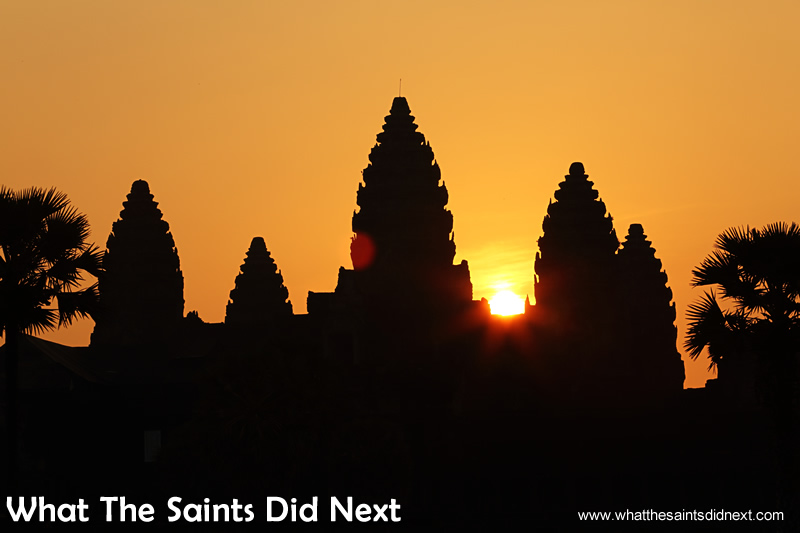The magic moment as the sun peeks through the lotus towers of the Angkor Wat temple.