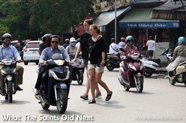 The serious look of concentration from tourists crossing the 'river.'  Crossing The Street In Hanoi Vietnam.