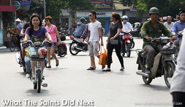 These two have chosen their moment well.  Crossing The Street In Hanoi Vietnam.