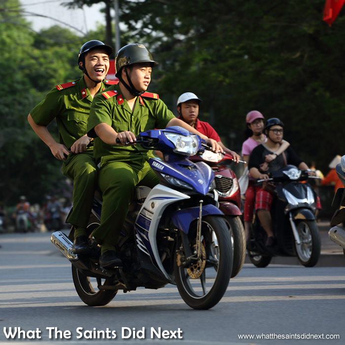 Military soldiers in Hanoi share a joke while driving through the city.