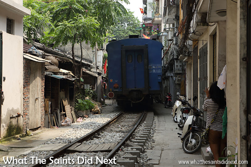 The back of the train as it rumbles away heading for Ho Chi Minh. Train track running through the narrow Train Street in Hanoi.