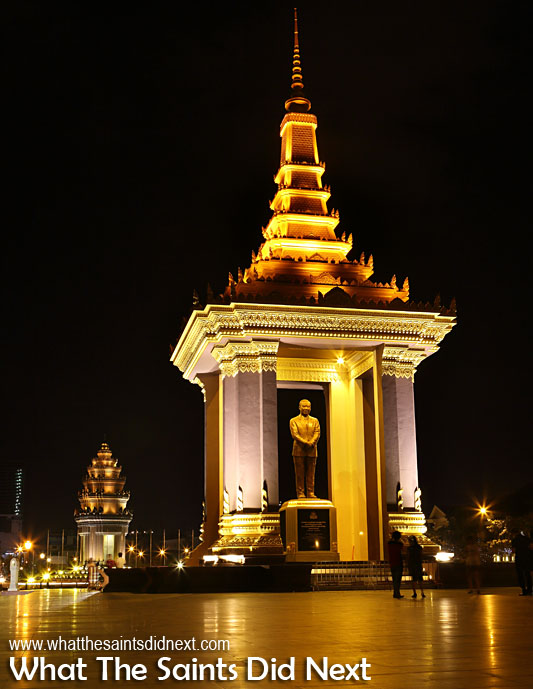 King Norodom Sihanouk's statue in Neak Banh Teuk Park at night, Phnom Penh, Cambodia. Victory Monument can be seen in the background. Cambodia Independence Day celebrations will be focused around this park.