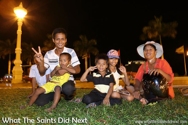 A Cambodian family joining the hundreds of people who gather in the park on the Riverfront in Phnom Penh, just relaxing and enjoying social time together. Celebrating Cambodia Independence Day With Night Photography In Phnom Penh.