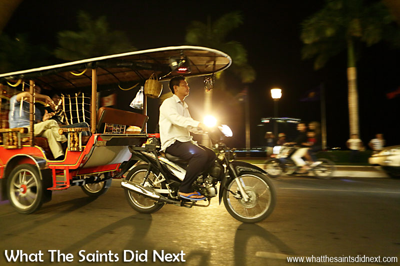 A tuk tuk taxi with a late night fare travelling through the middle of Phnom Penh.