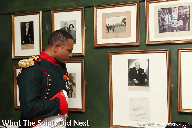 """A display of photographs inside Longwood House, St Helena, showing famous visitors over the years. Although Sir Winston Churchill never visited he did send this signed photograph and letter in 1961 as a thank you for Napoleon """"relics"""" that were sent to him. The colour framed picture is of Prince Andrew signing the visitor's book in Longwood House in 1984 and alongside this is a picture of his father, Prince Phillip, walking in Longwood House grounds."""