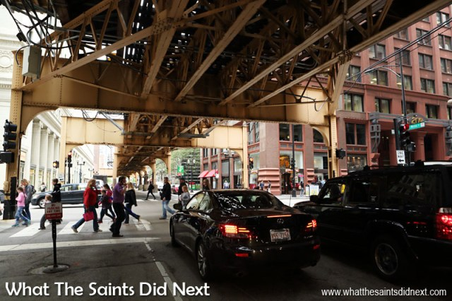 The Union elevated railway loop running overhead, cars and pedestrians below. The Chicago multi-level road system was developed from traffic patterns in the Loop. Local traffic tends to use the upper, street level roads, while through traffic and delivery and heavy goods vehicles make use of the lower levels.