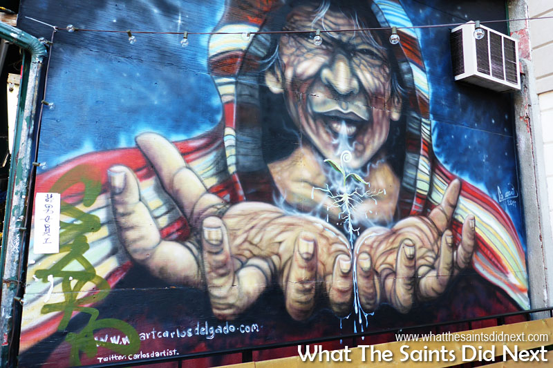 Attraction to this mural was powerful with the beckoning hands and aged lines of the wise face. Note the twitter account of the graffiti artist.