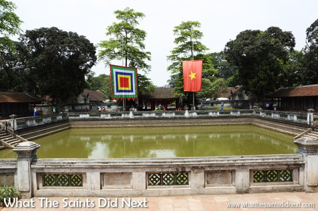 Temple of Literature, Hanoi, Vietnam. The distinctive Vietnamese flag (right) and the festival flag of the Five Elements flutters over the Well of Heavenly Clarity. To the left and right are the rows of stelae of doctors.