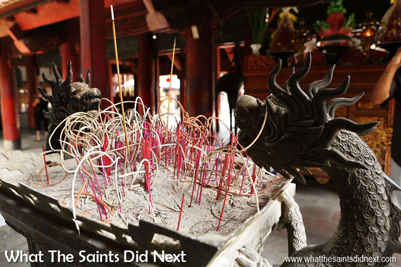 Incense sticks burning under the watchful gaze of a pair of dragons. Dragons are one of Vietnam's holy creatures along with tortoises, unicorns and phoenixes.