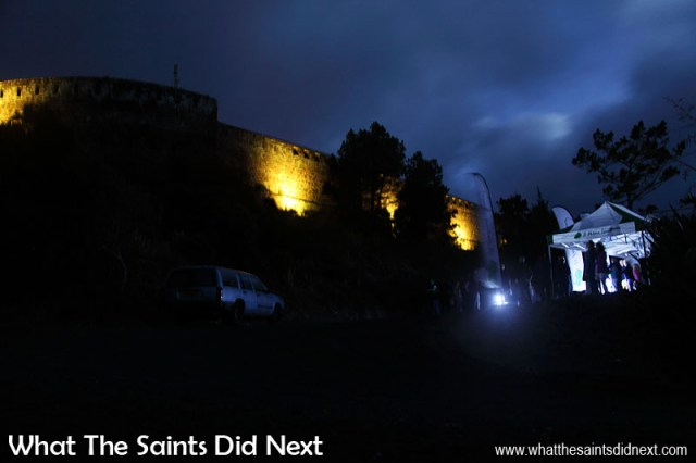 The view from up close. Guests at the High Knoll car park gaze upwards as the first sequence of colours illuminates the old stone walls. High Knoll Fort lights, St Helena.