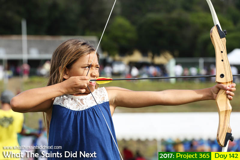 Young woman archer on Francis Plain, St Helena Island, taking aim with a bow and arrow.