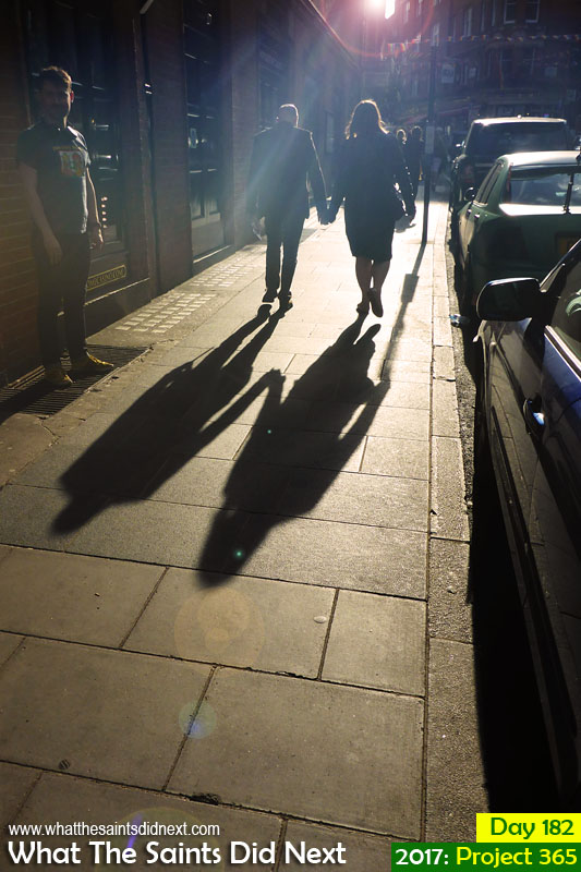 London street photography throwing long shadows on the pavement.