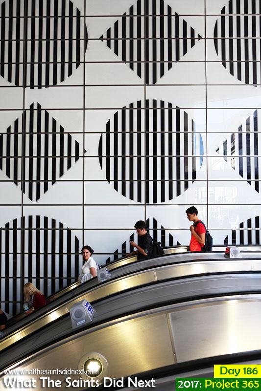 Riding the escalators on the Tottenham Court Road underground station, London.