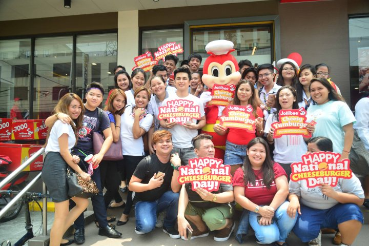 Students pose with YouTubers Baninay Bautista and Teejay Marquez outside Jollibee Legarda-Bustillos after getting their FREE Cheesy