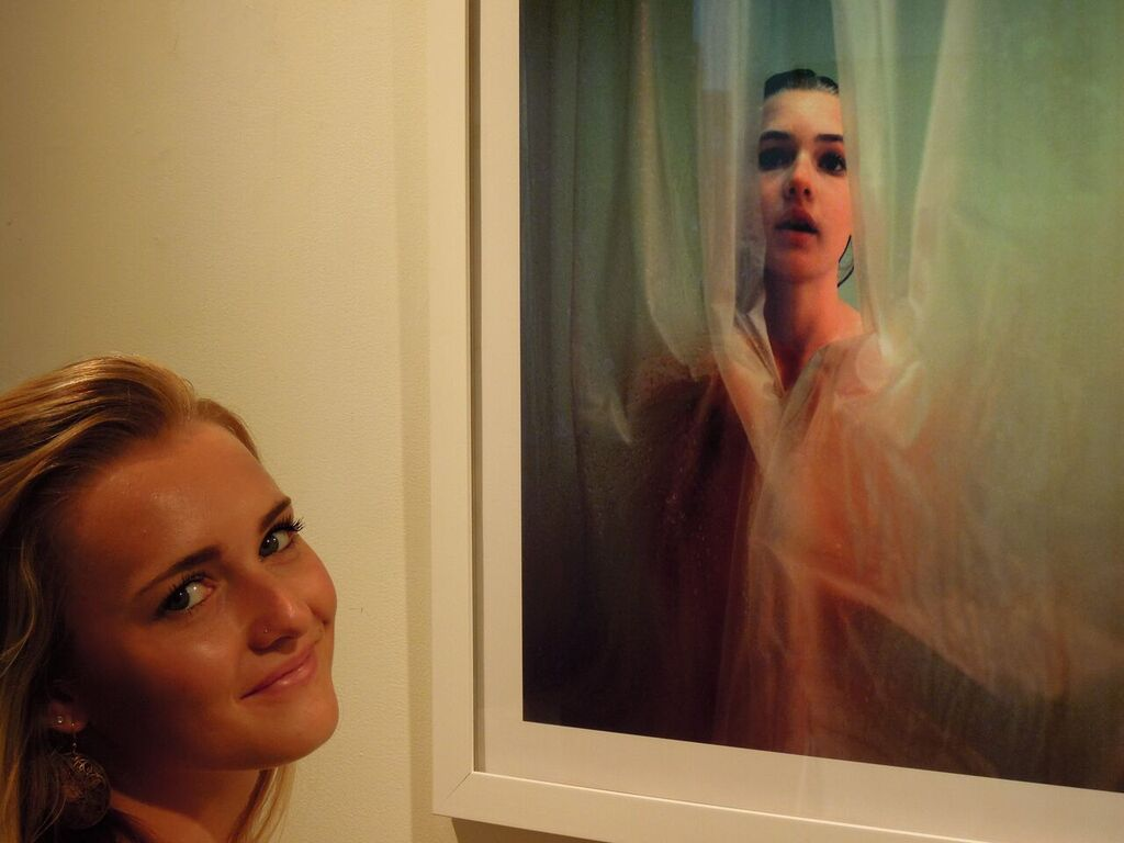 """Zoe at age 20, with the portrait """"Shower, 2008"""" by Nancy Grace Horton, in a photo from the NESOP exhibit opening on May 13, 2015 (photo courtesy of Bill Paarlberg)."""