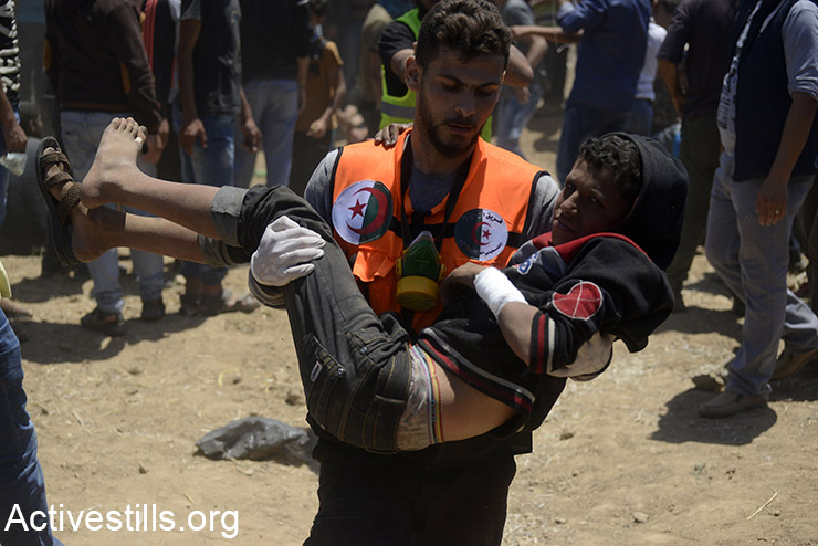 A medic carries a Palestinian child during a protest in the Gaza Strip, as part of the Great March of Return, May 14, 2018. (Mohammed Zaanoun/Activestills.org)