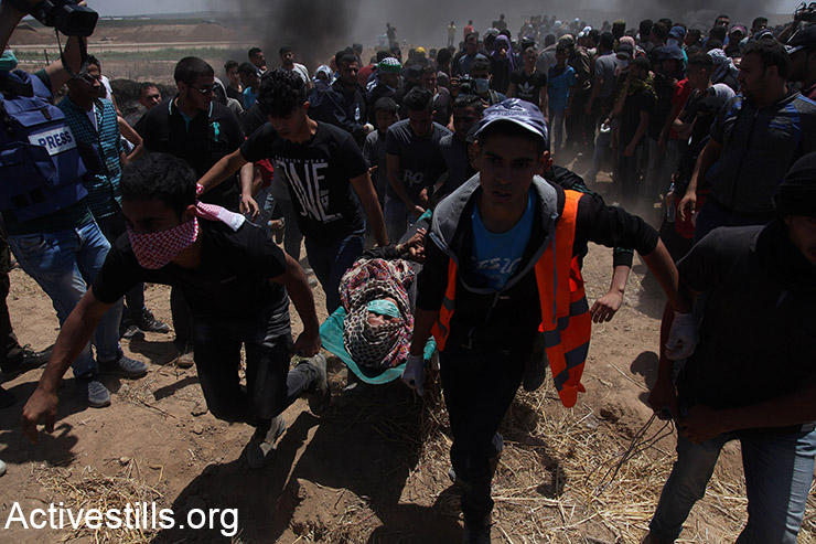 Medics evacuate a Palestinian protester who was shot by Israeli snipers during protests inside the Gaza Strip, May 14, 2018. (Mohammed Zaanoun/Activestills.org)