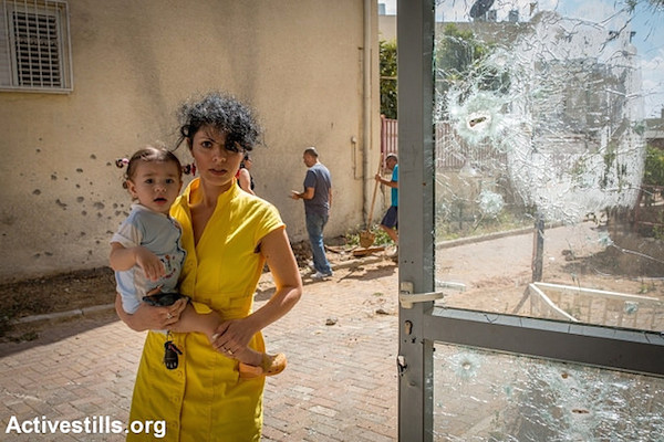 Woman near shattered window caused by a Hamas rocket on July 15, 2014 in the town of Sderot, Israel. (Photo by Activestills.org)