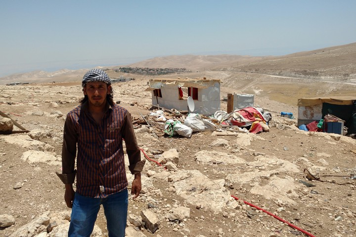 Harba Hamadin, a resident of the Bedouin community Abu Nawar, stands in front of the buildings demolished by Israeli authorities in his village, July 10, 2018. (Orly Noy)
