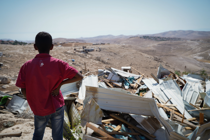 A child looks on at the remains of demolished homes in the Palestinian village of Khan al-Ahmar, July 4, 2018. (Yaniv Nadav/Flash90)