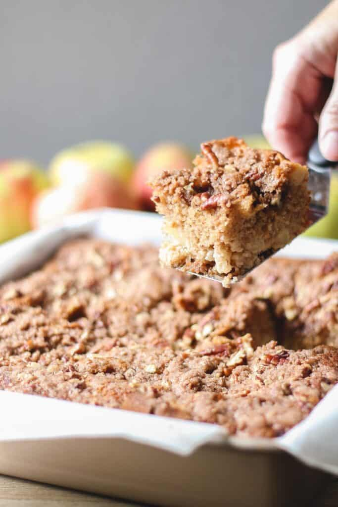 Apple cake in a parchment lined pan, a piece being lifted out with a spatula