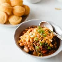 a bowl of chili with cheddar cheese and green onions on top. Mini cornbread muffins in background.