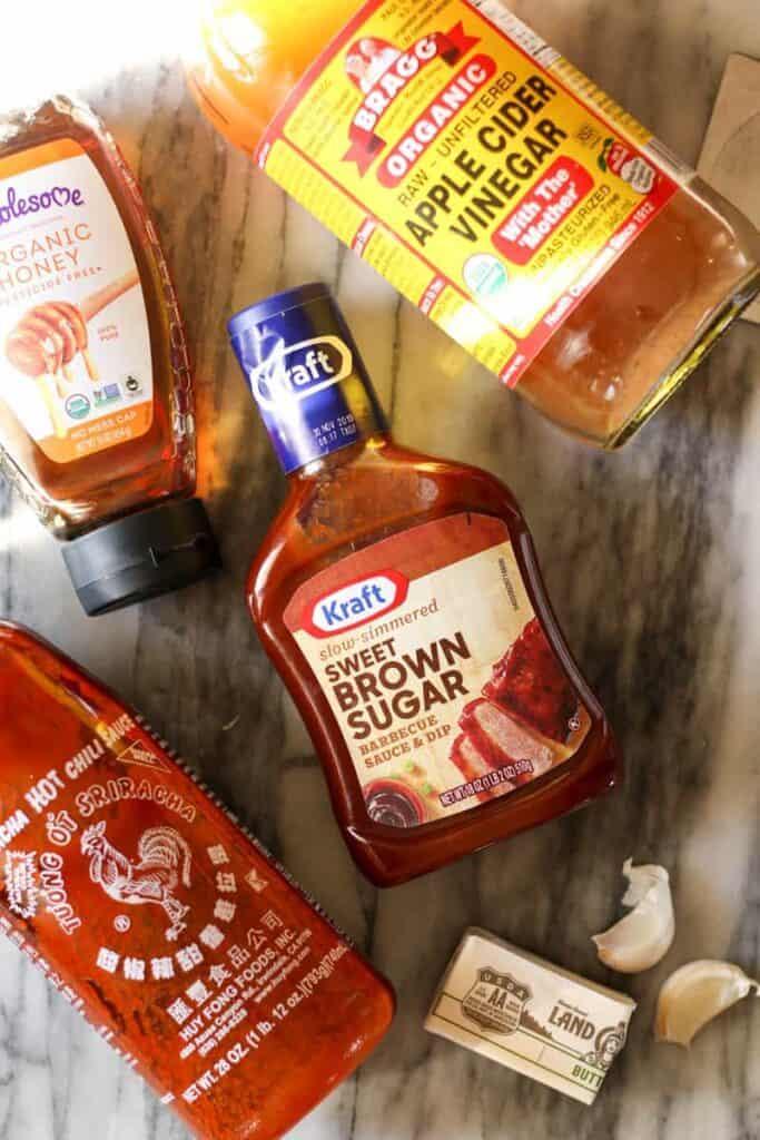 ingredients for honey sriracha bbq sauce, bbq sauce, apple cider vinegar, honey, sriracha, garlic, and butter