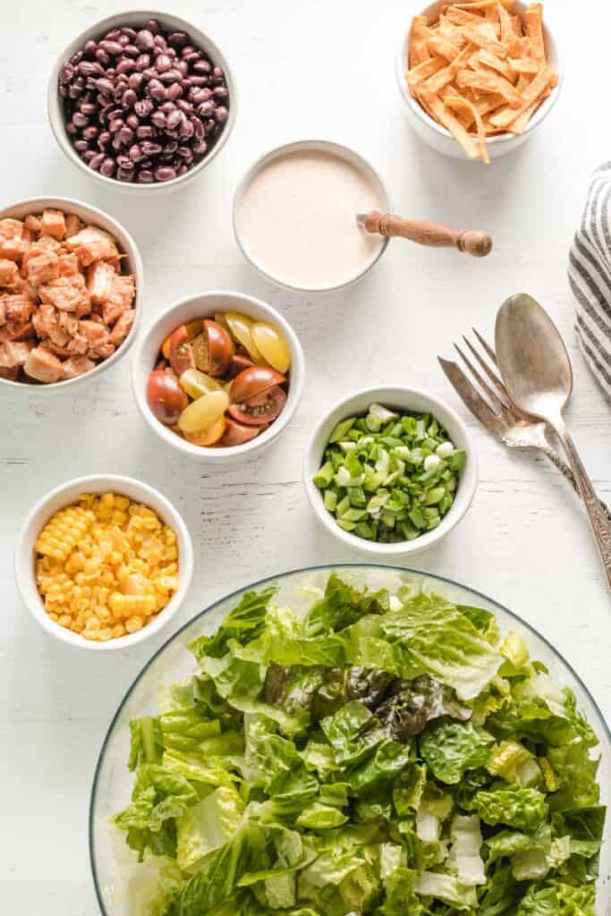 Salad ingredients laid out in bowls, beans, corn, lettuce, chips, chicken, and salad dressing.