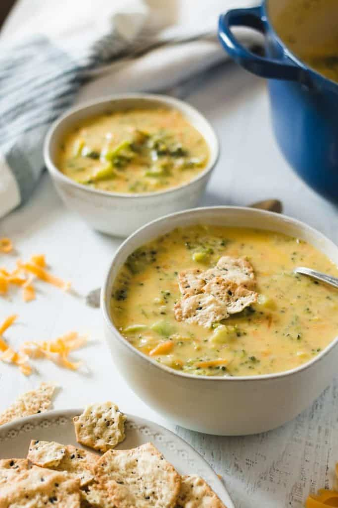 Two bowls of gluten free broccoli cheddar soup. Blue pot in background.