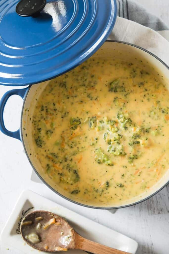 A big blue Le Crueset pot filled with broccoli cheddar soup.