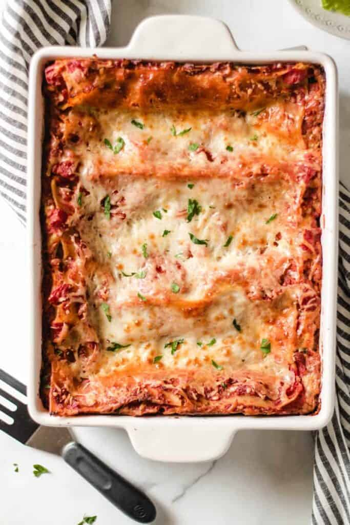 A pan of lasagna in a white casserole dish, with a striped towel.