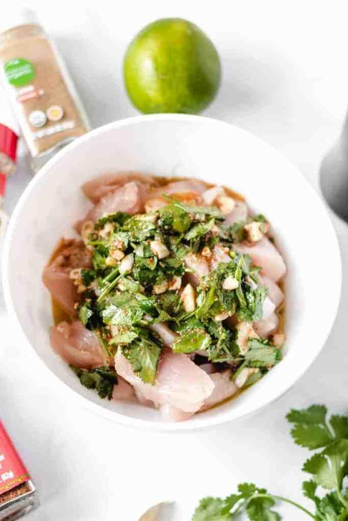 Fajita marinade with lots of cilantro over chicken strips in a white bowl.