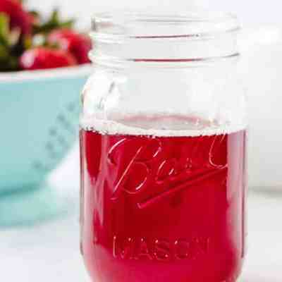 Bright red strawberry simple syrup in a glass mason jar.