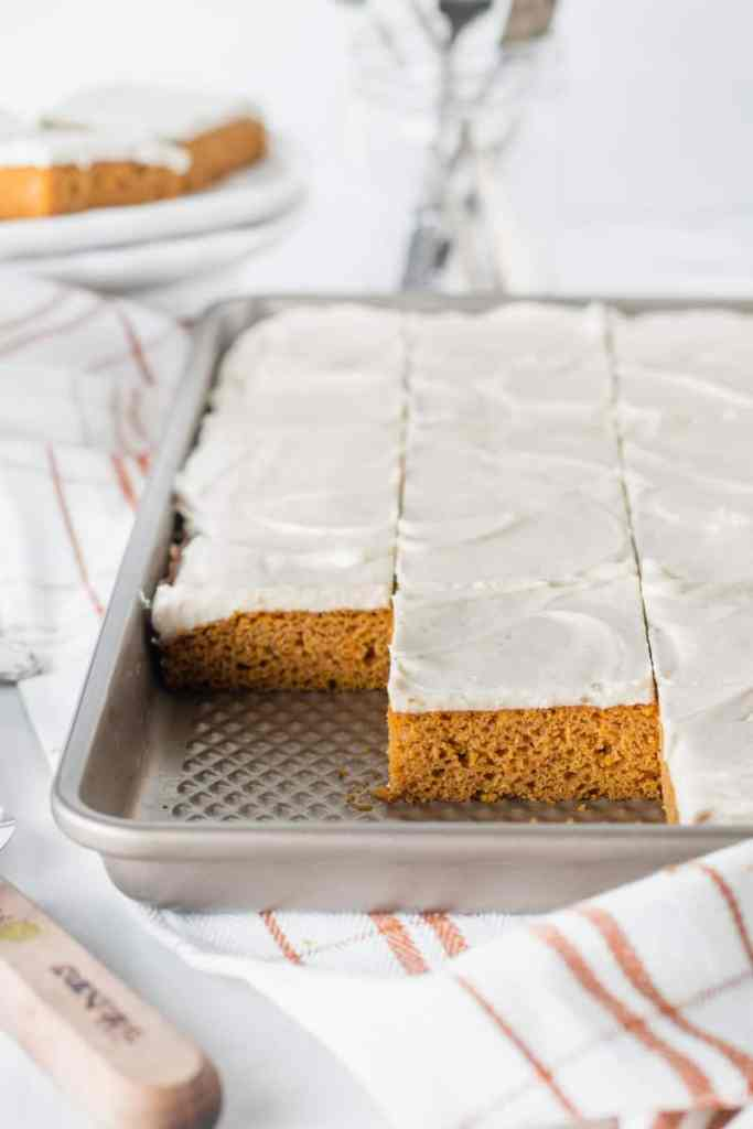 A sheet pan with sliced frosted pumpkin bars. Several missing to show texture of cake.
