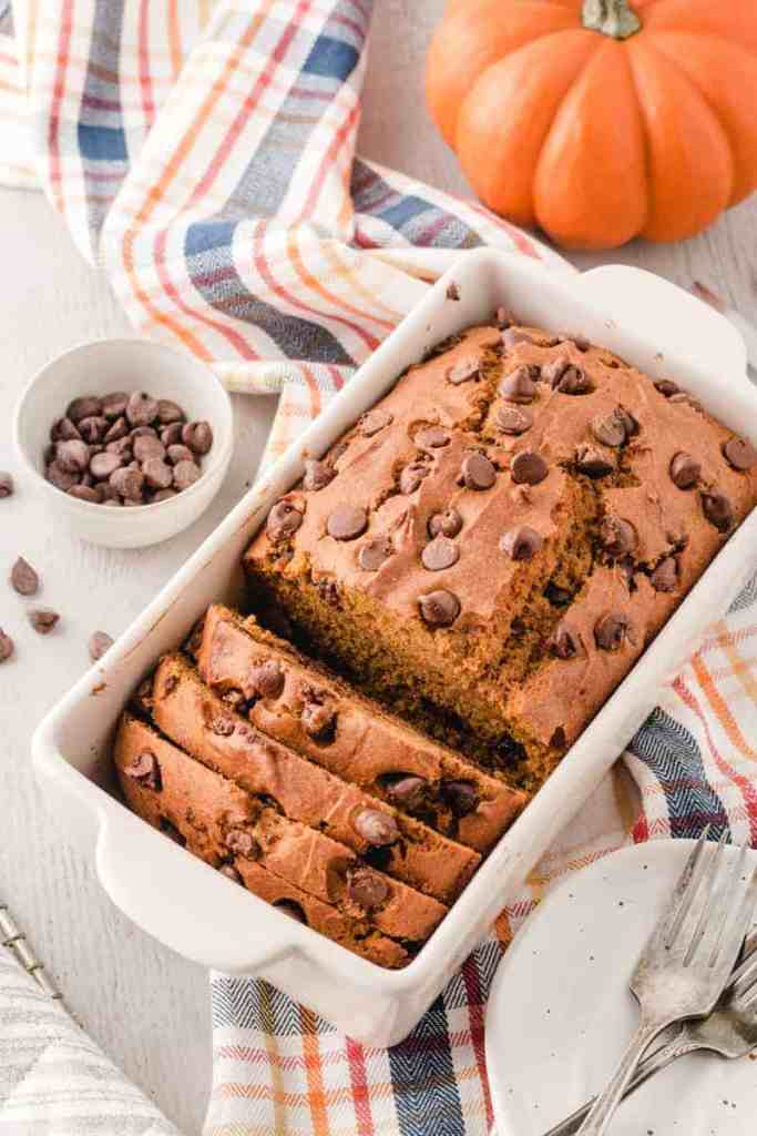A loaf of Gluten-free Chocolate Chip Pumpkin Bread, partially sliced, in a Rae Dunn Loaf pan.