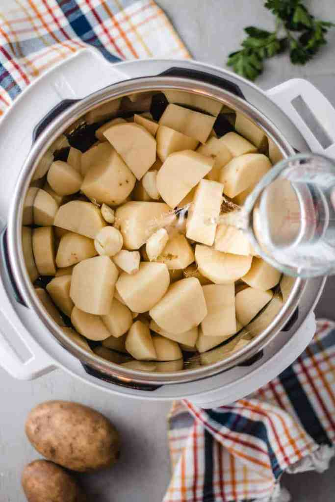 Pouring water over diced potatoes in the instant pot.
