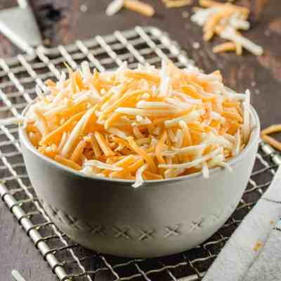 A bowl of shredded cheese on a vintage cheese grater.