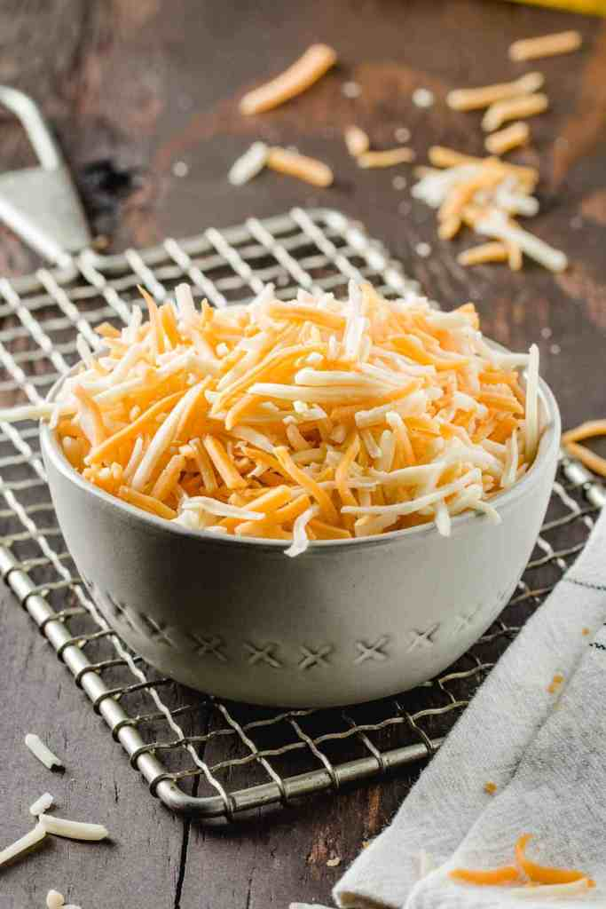A bowl of shredded cheese on a vintage acme cheese grater.