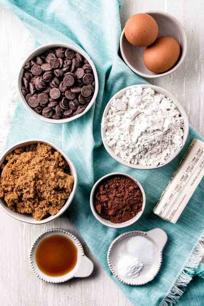 Ingredients in gluten-free double chocolate chip cookies measured out in bowls on a teal napkin.
