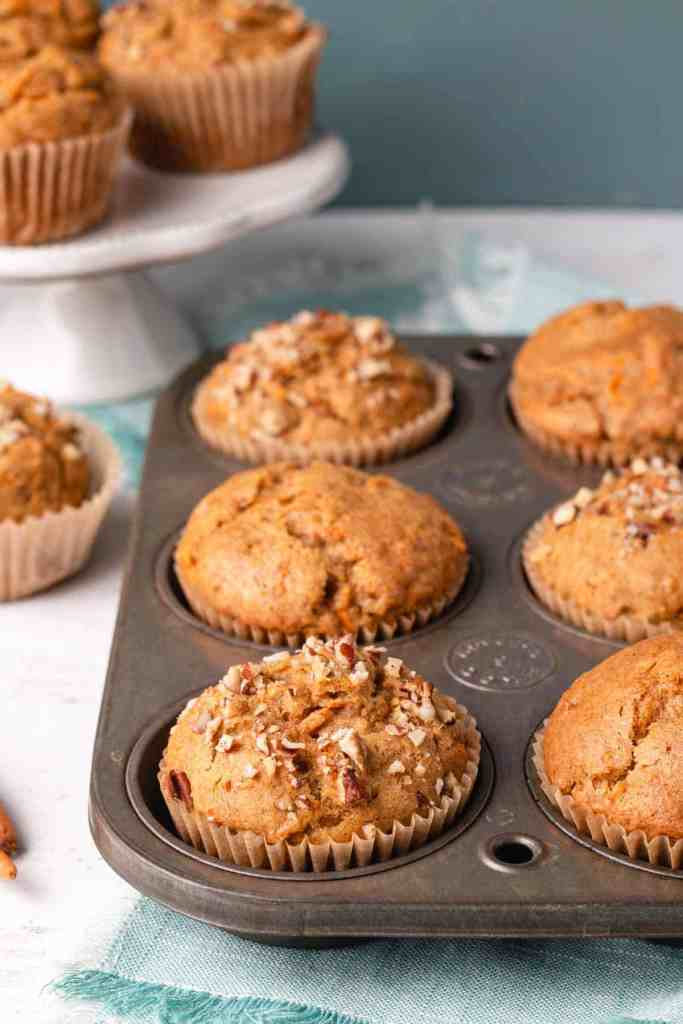Gluten-free Carrot Muffins in vintage ecko tin with pecans sprinkled on top for texture and crunch.