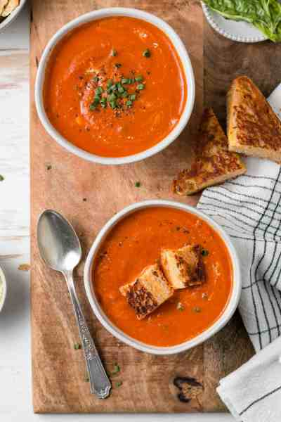 Gluten-free tomato soup in bowls with chives and grilled cheese.
