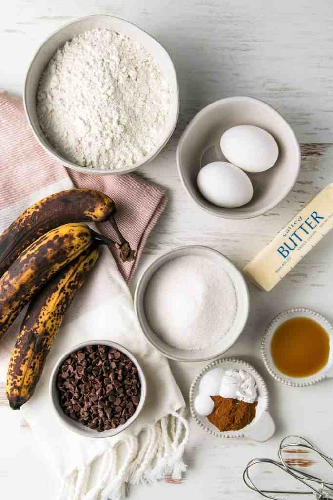 Ingredients for gluten-free chocolate chip banana muffins measured out in bowls next to three over-ripe bananas.