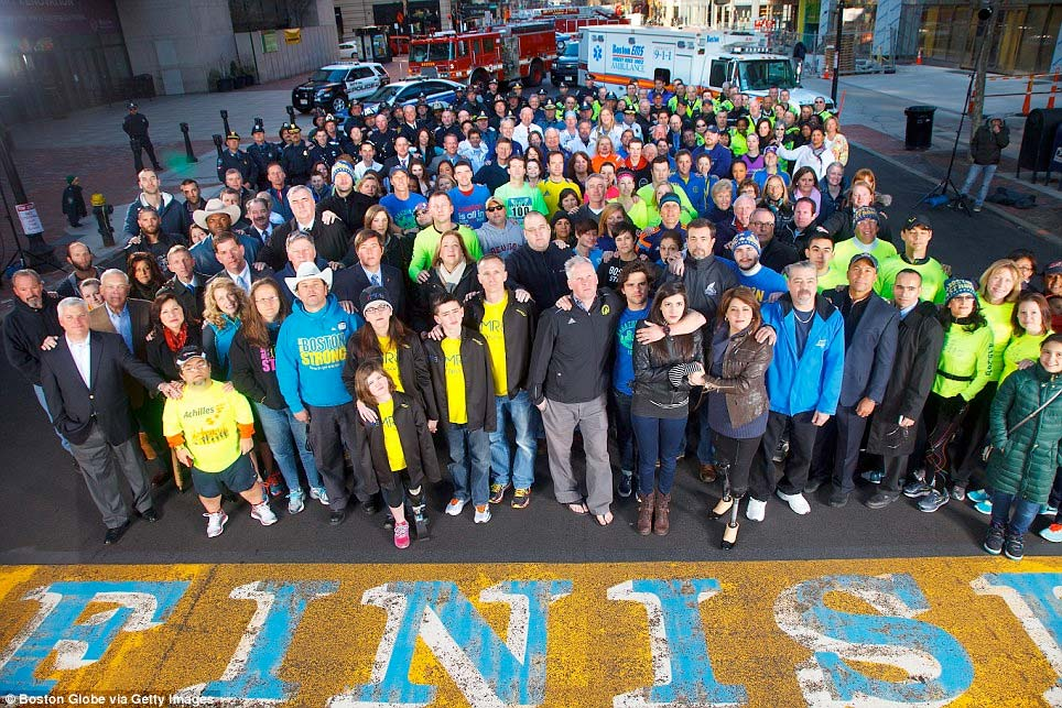 Photo Description: Survivors of the Boston Marathon bombing, gathered at the finish line one year after the attack.