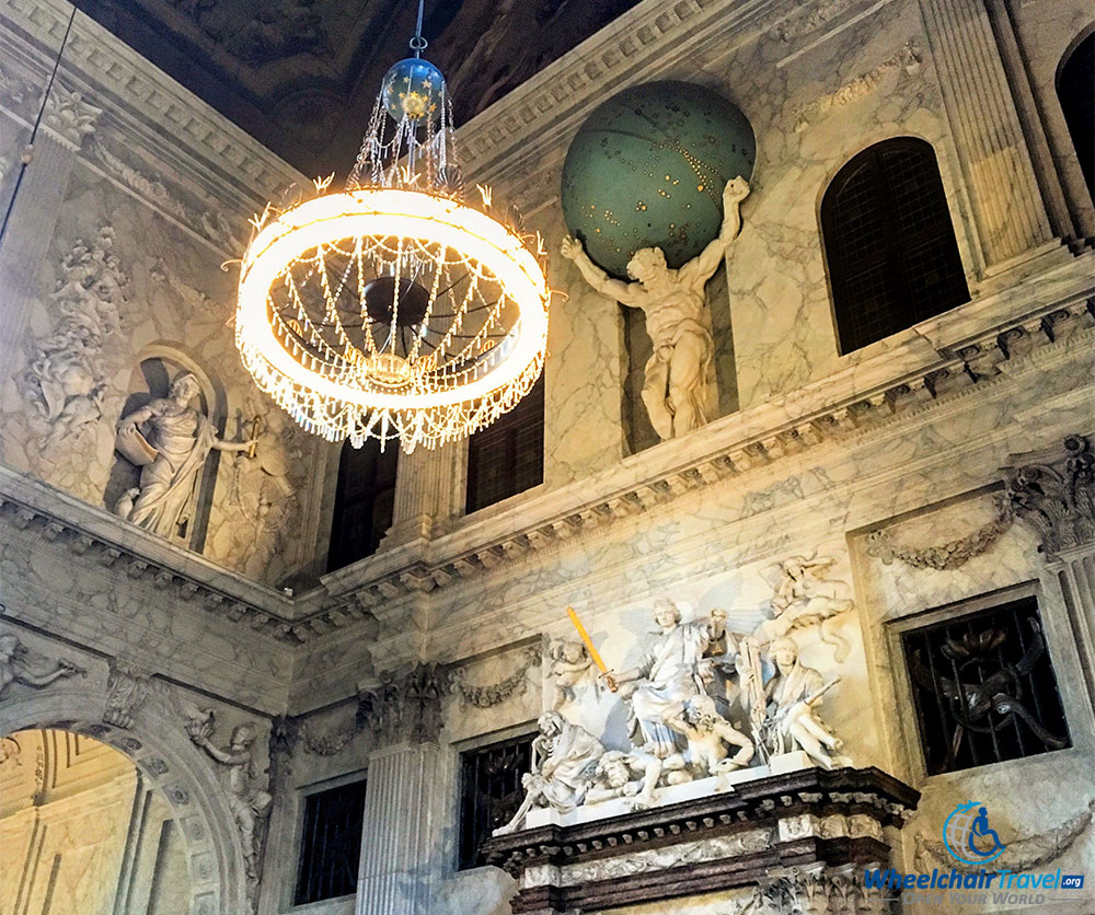 PHOTO DESCRIPTION: A marble sculpture of Atlas with the earth on his shoulders, set high on a wall near to the ceiling in the great hall.