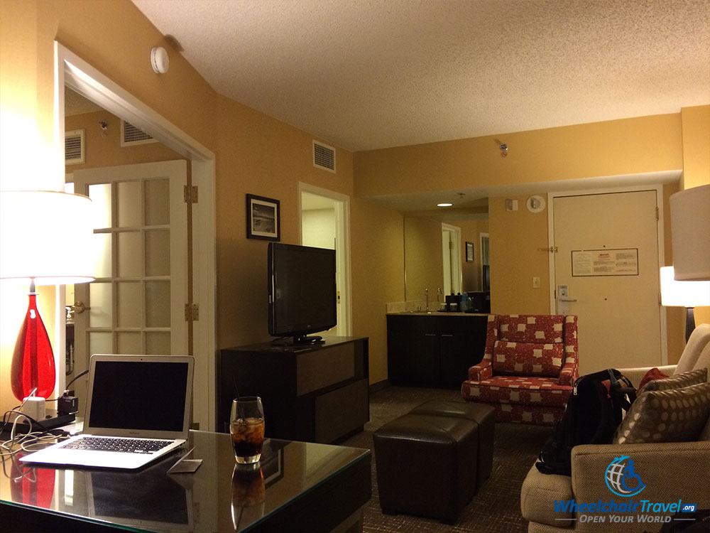 PHOTO DESCRIPTION: The room's living area seen from the opposite direction and behind the desk, with a doorway to the bathroom and a wetter at the far end.